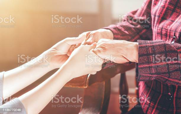 Teenage Asia Young Girl Carer Holding Grandma Hands Concept Of Helping Care For The Elderly Life With Dark Background Close Up Copy Space Cropped View Stock Photo - Download Image Now