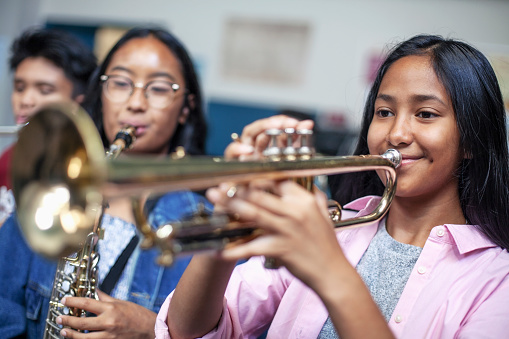 Confident teenage girl playing trumpet in musical class. Female students are learning music at high school. They are practicing woodwind instrument.