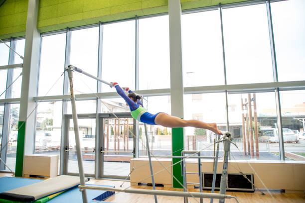 teenage athlete excercising on bars - uneven parallel bars stock photos and pictures