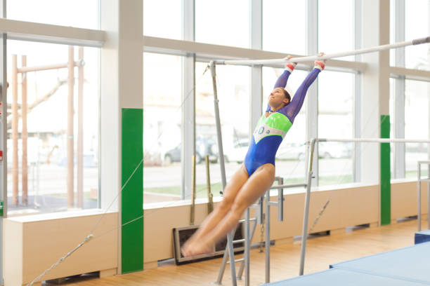 teenage athlete exercising on uneven parallel bars - uneven parallel bars stock photos and pictures
