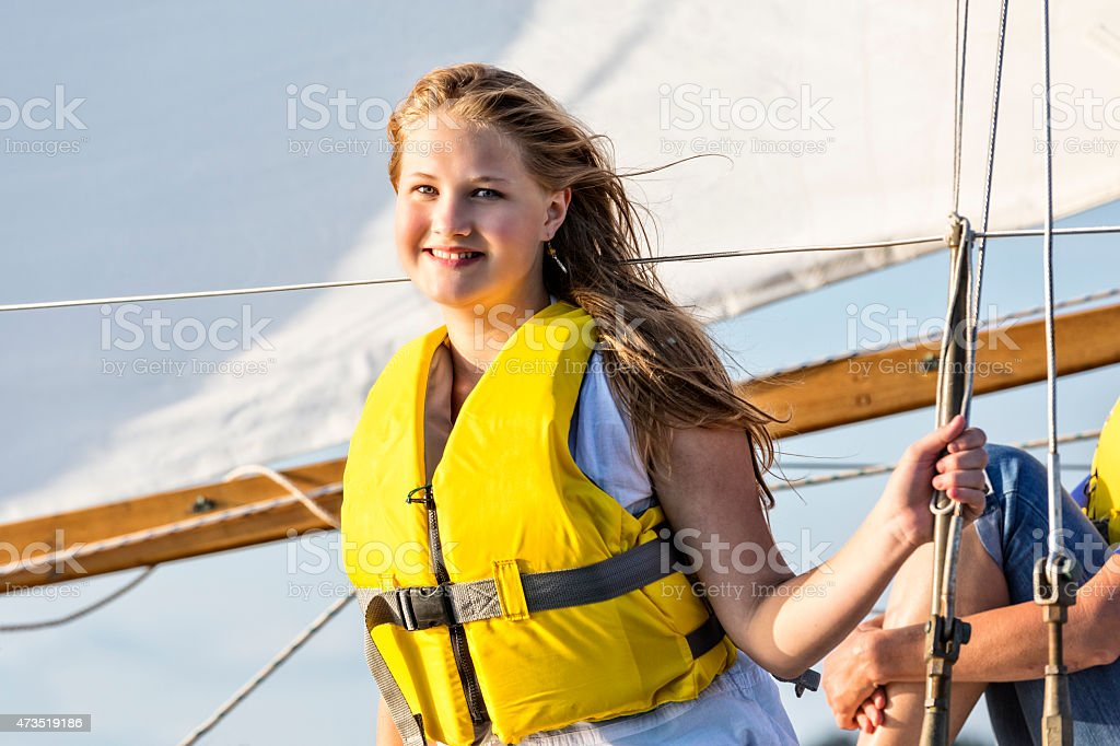 Teenage Beautiful Girl Holds on While Sailing on a Boat stock photo