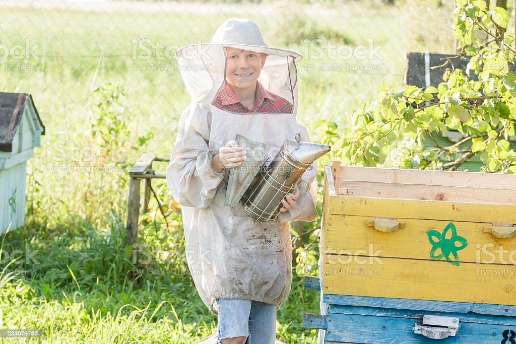 Teenage beekeeper checking hives on bee yard stock photo