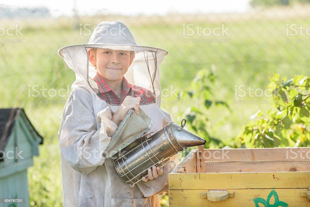 Teenage beekeeper wearing protective clothing stock photo