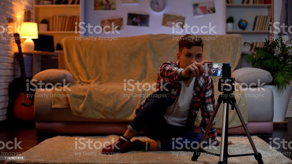 Teenage boy adjusting camera on smartphone for recording videoblog, hobby Teenage boy adjusting camera on smartphone for recording videoblog, hobby Adult Stock Photo