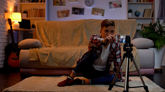 Teenage Boy Adjusting Camera On Smartphone For Recording Videoblog Hobby Stock Photo - Download Image Now