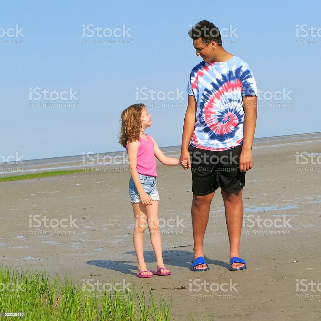 Teenage Boy and Child Holding Hands on Beach stock photo