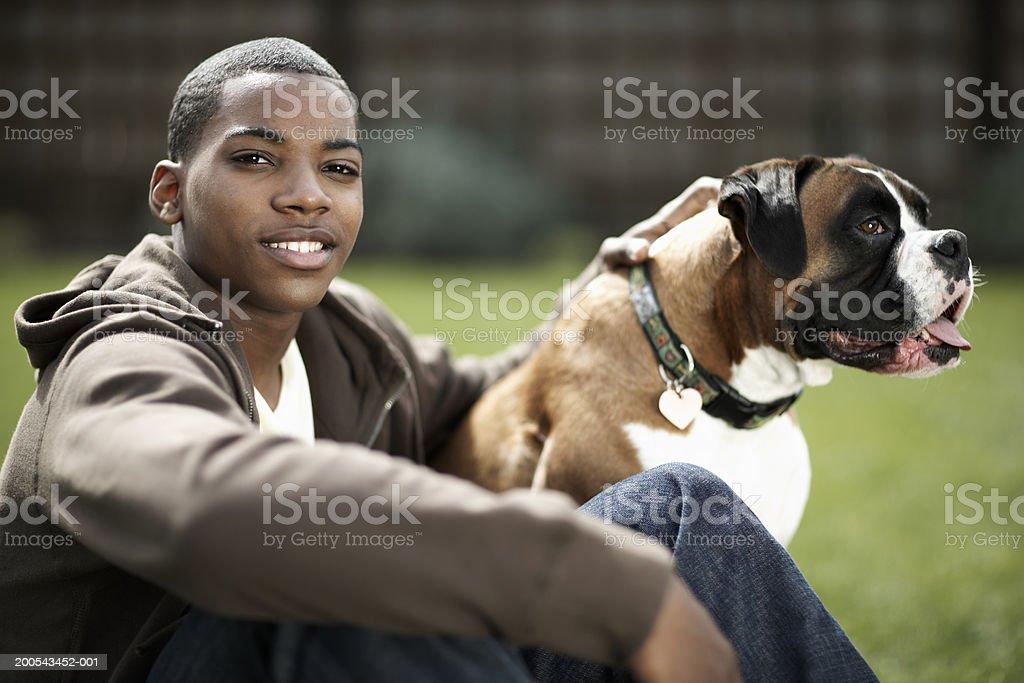 Teenage boy (14-16) and dog outdoors, boy smiling stock photo