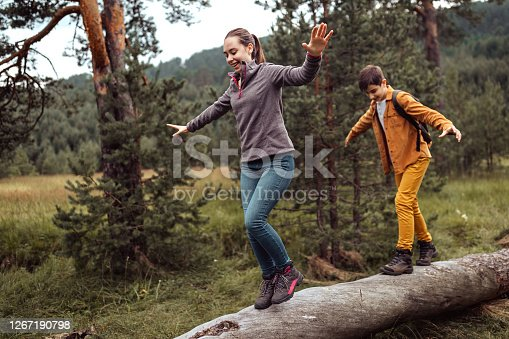 Teenage boy and girl having fun balancing on fallen tree trunk at forest