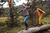 istock Teenage boy and girl balancing on fallen tree at forest 1267190798