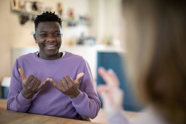Teenage Boy And Girl Having Conversation Using Sign Language Teenage Boy And Girl Having Conversation Using Sign Language signing stock pictures, royalty-free photos & images