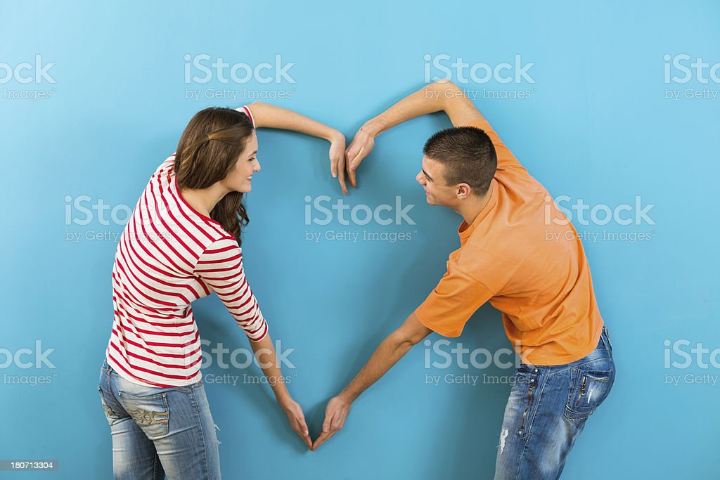 Teenage boy and girl making heart shape with hands royalty-free stock photo