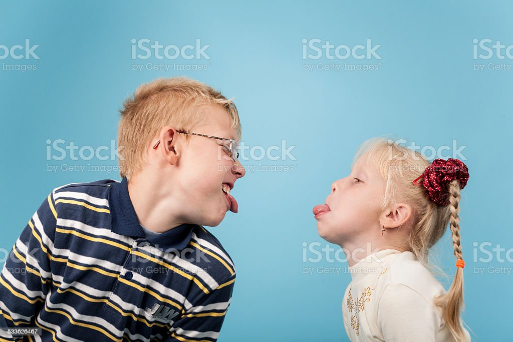 Teenage boy and girl stick out tongues to each other stock photo