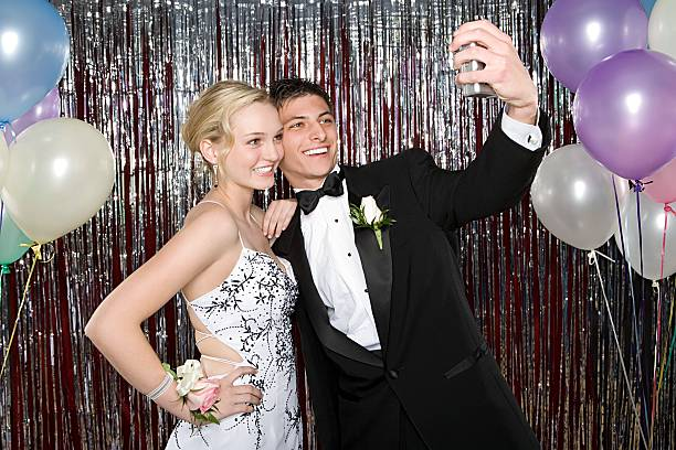 teenage boy and girl taking a picture at prom - prom stock photos and pictures