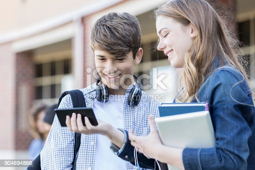 istock Teenage boy and girl use cell phone between classes 904694866