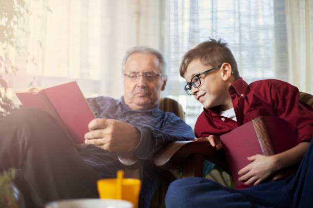 teenager-jungen und seinem großvater, ein buch zu lesen - haushaltsbuch führen stock-fotos und bilder