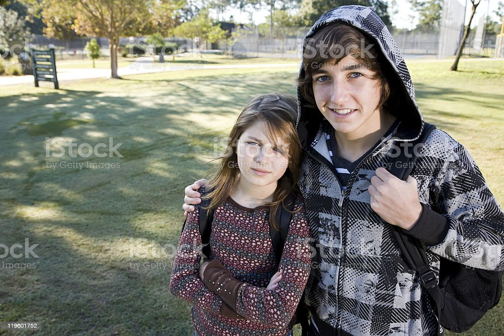 Teenage boy and young sister with school backpacks royalty-free stock photo