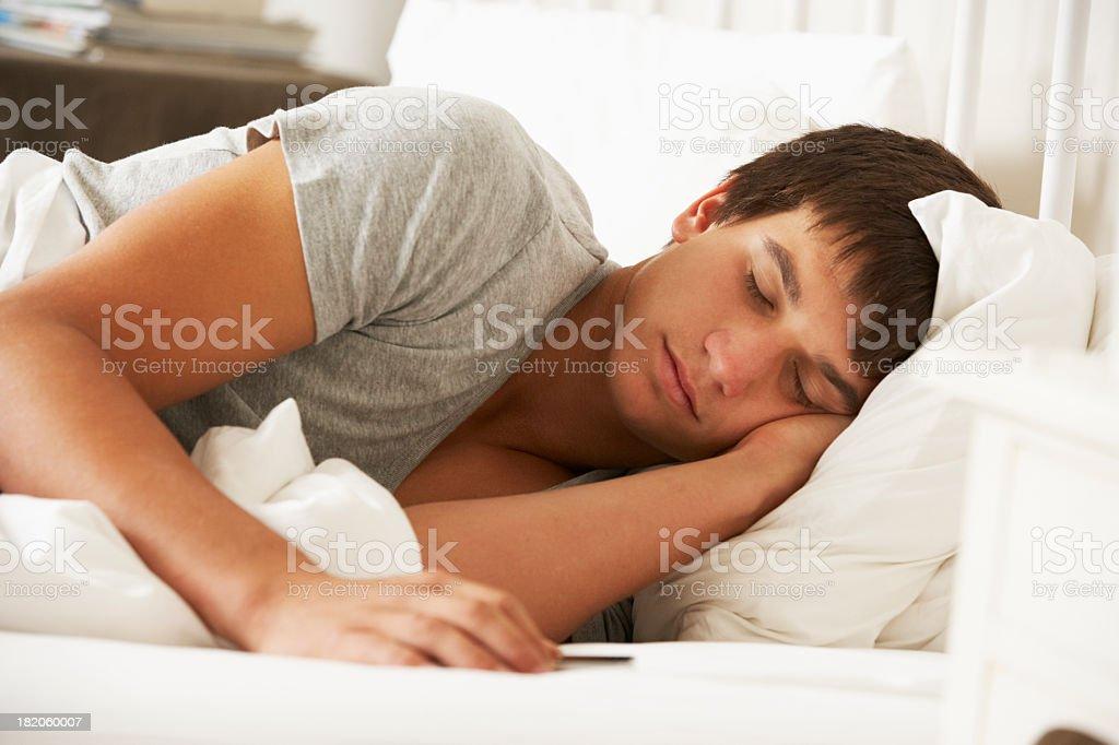 Teenage Boy Asleep In Bed At Home stock photo