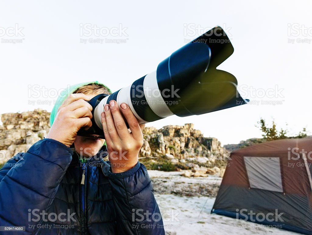 Teenage boy at campsite taking photographs with zoom lens stock photo