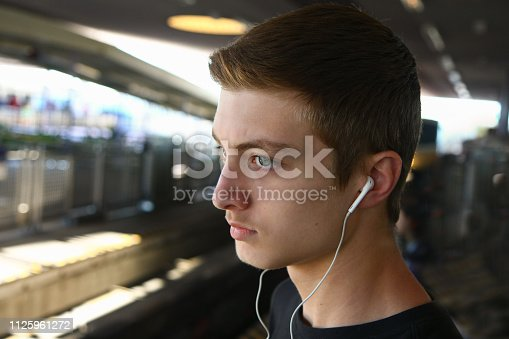 Boy standing at a railway station wearing earbuds.