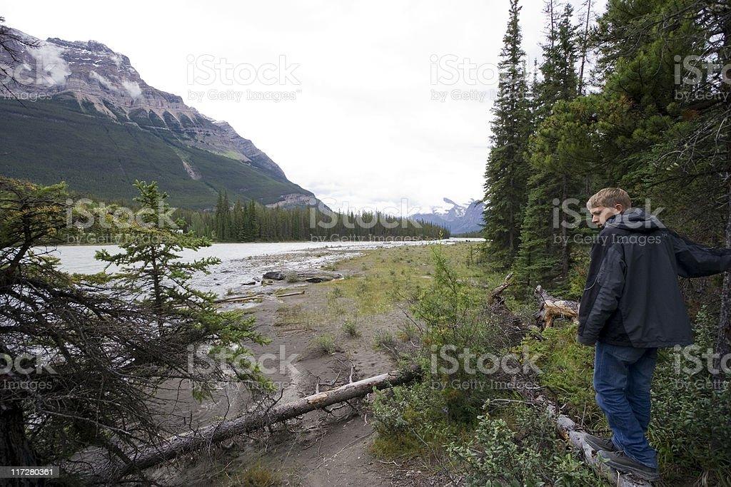 Teenage boy at riverbank stock photo