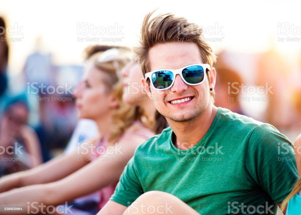 Teenage boy at summer music festival, sitting on ground stock photo