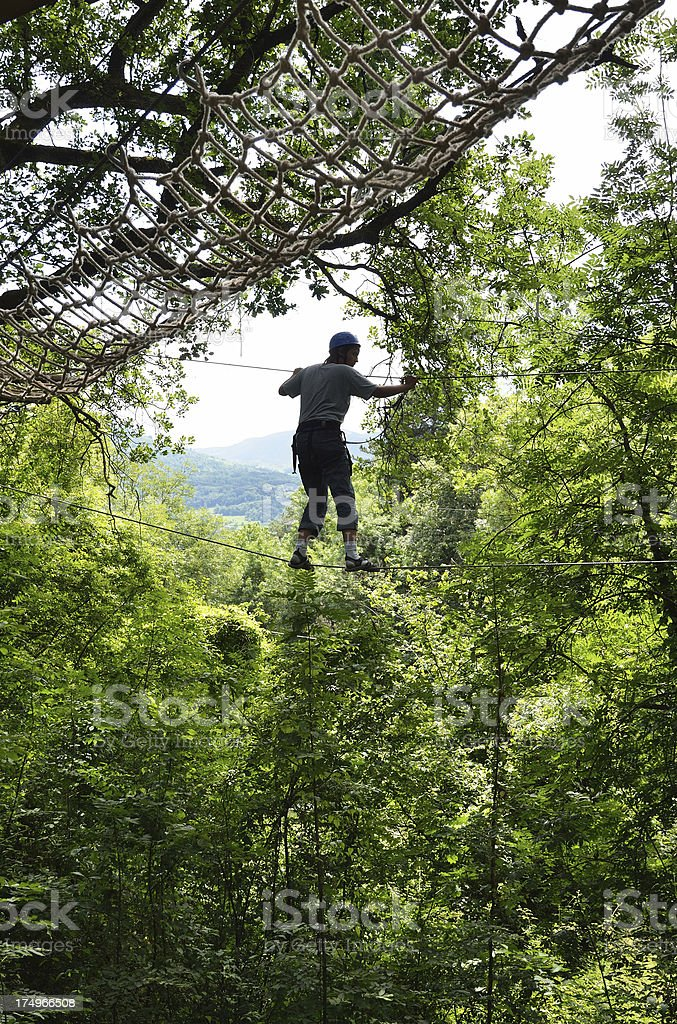 Teenage boy at the rope parkour high up stock photo