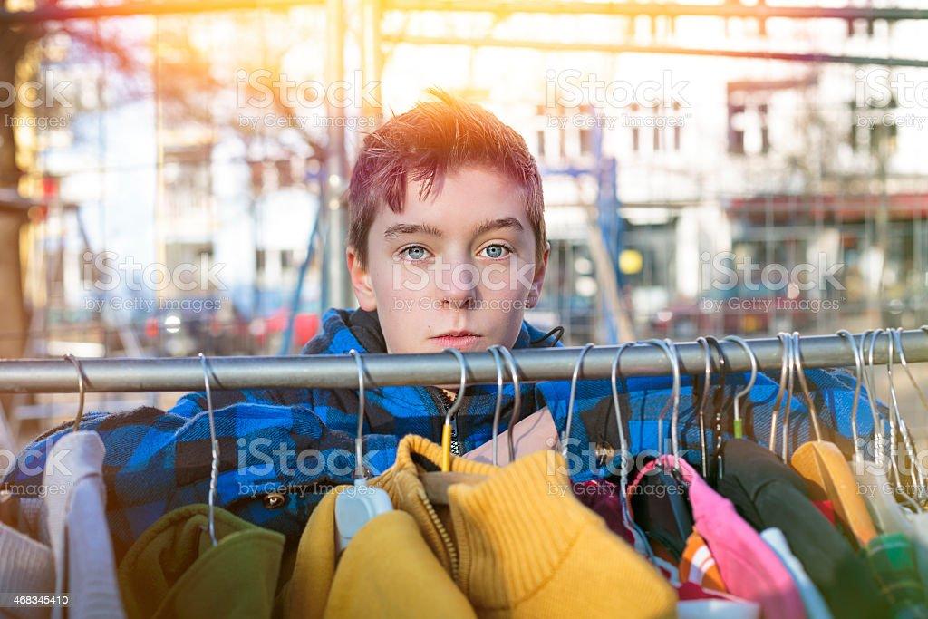 teenage boy behind a clothes rail on a flea market royalty-free stock photo