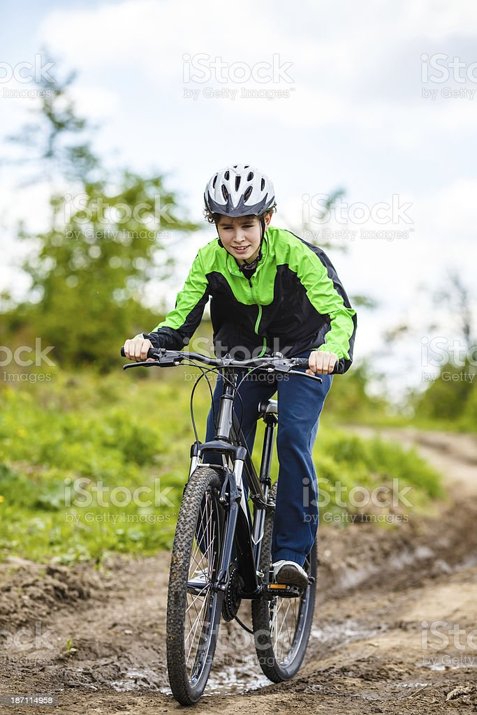 Teenage boy biking on forest trails royalty-free stock photo