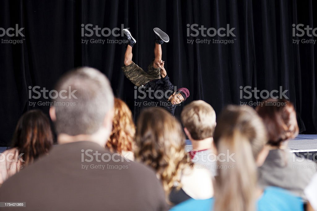 Teenage boy break dancing on  stage for an audience stock photo