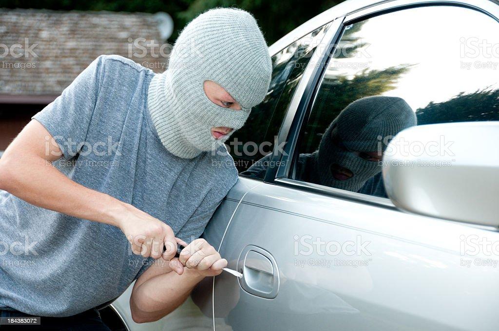 Teenage boy breaking into a car stock photo