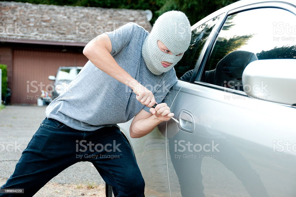 Teenage boy breaking into a car stock photo