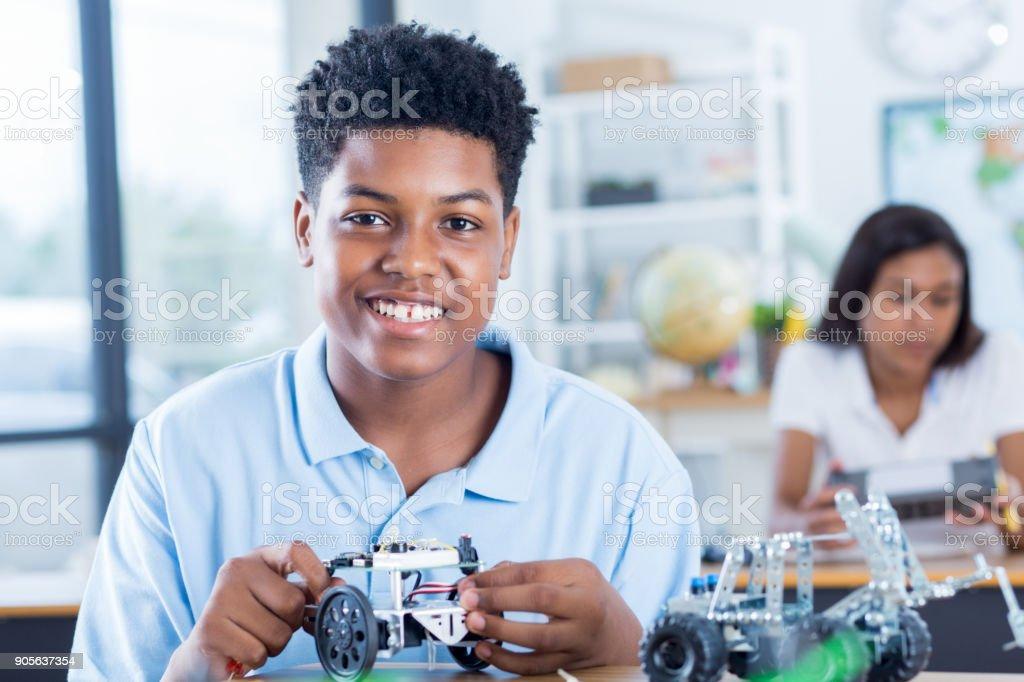 Teenage boy builds robot model at school stock photo