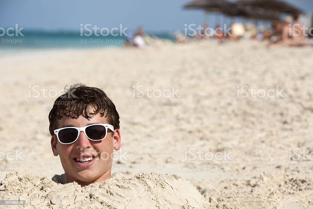 teenage boy buried in sand stock photo