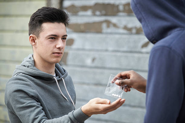 Teenage Boy Buying Drugs On The Street From Dealer Teenage Boy Buying Drugs On The Street From Dealer drug dealer stock pictures, royalty-free photos & images