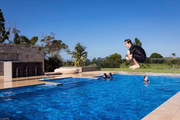Teenage Boy Cannonballing Into Swimming Pool stock photo