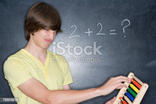 istock A teenage boy counting on an abacus 79334619