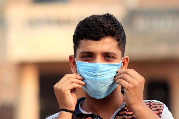Teenage boy covering his face with pollution mask against COVID-19 stock photo