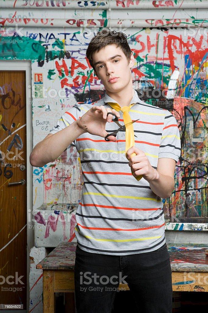 Ein Teenager junge Schneiden Krawatte in half Lizenzfreies stock-foto