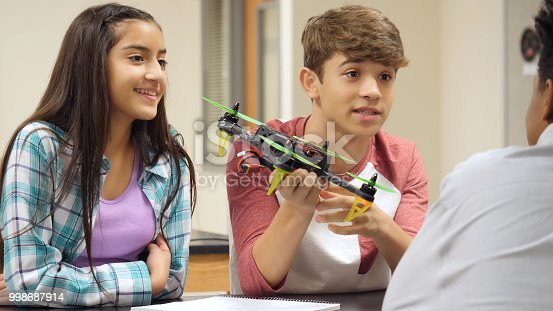 istock Teenage boy discusses hovercraft project with classmates 998687914