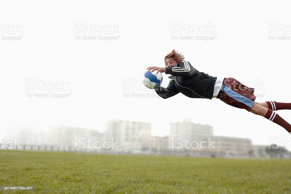 Teenage boy (14-15) diving to catch football royalty free stockfoto