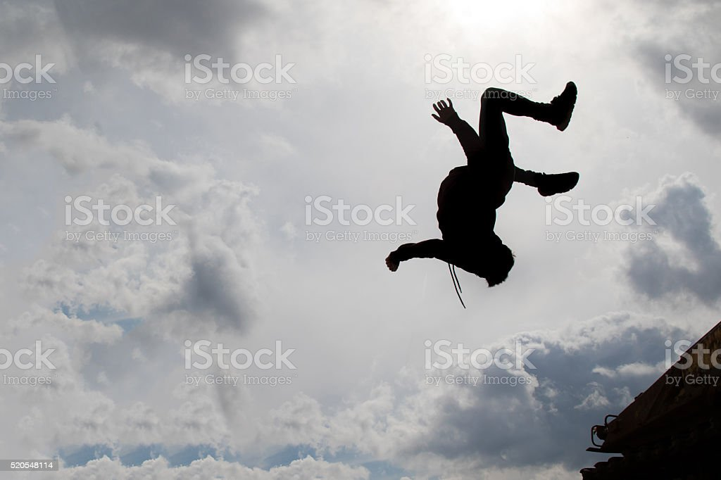 Teenage boy doing a back flip silhouetted stock photo
