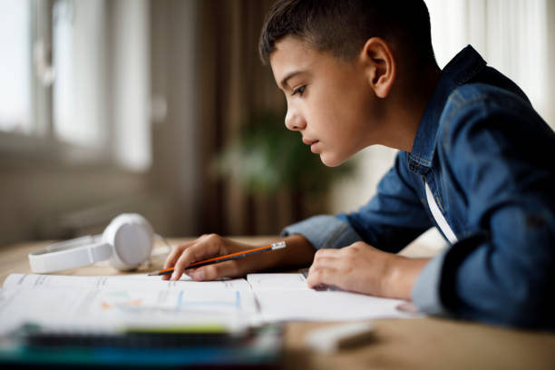 Teenage boy doing homework Teenage boy doing homework workbook stock pictures, royalty-free photos & images