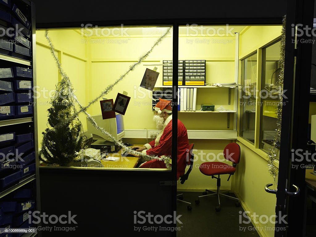 Teenage boy(16-17 years) dressed as santa using computer in office, side view royalty-free stock photo