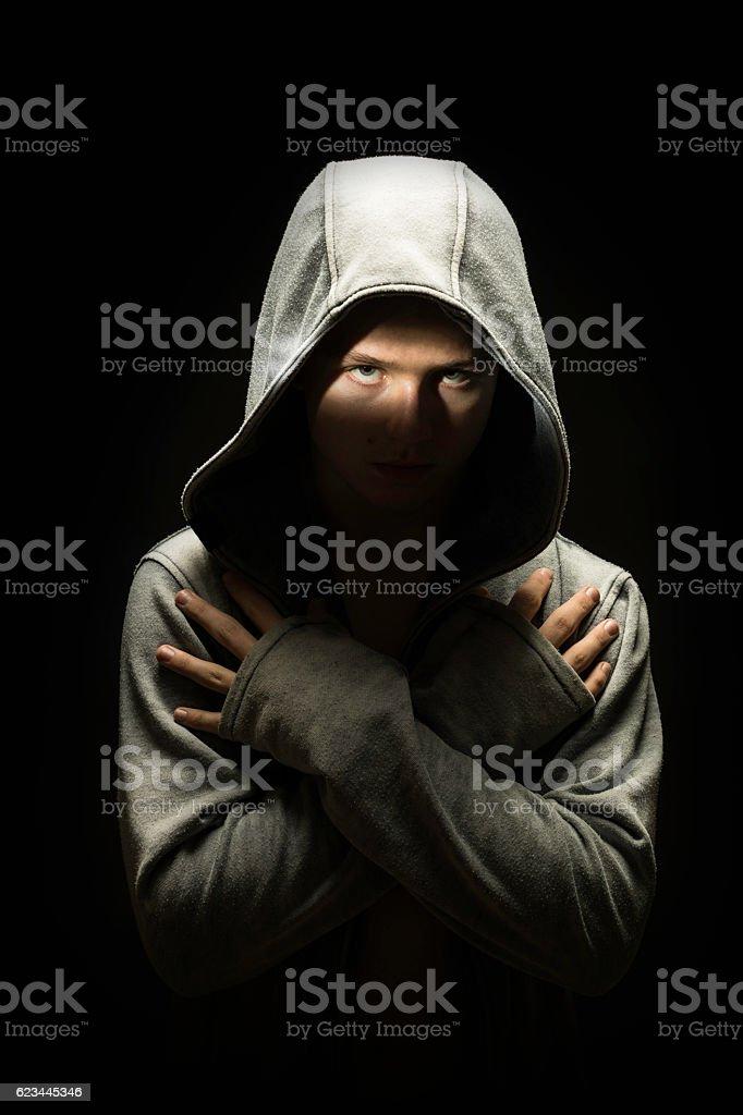 teenage boy dressed in hooded jacket in the dark stock photo