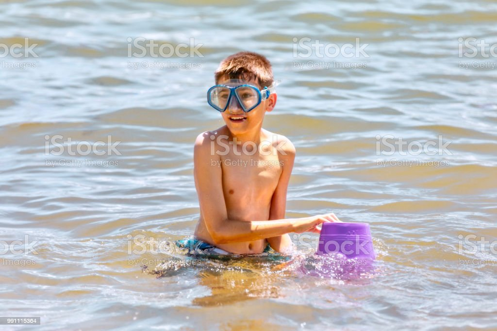 Teenage boy dumps out his bucket while looking for more crabs to catch stock photo