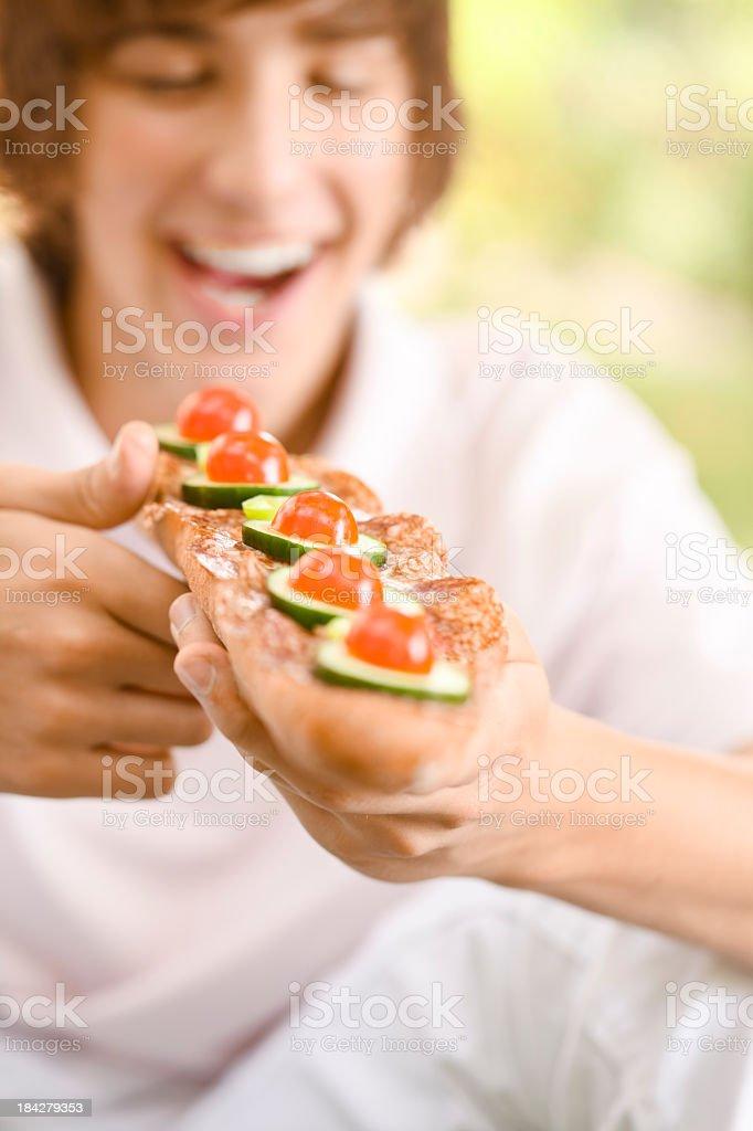 Teenage boy eating a sandwich royalty-free stock photo