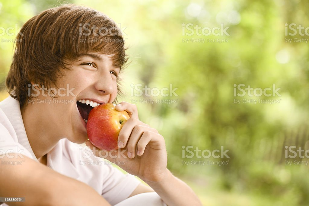 Teenage boy eating an apple stock photo