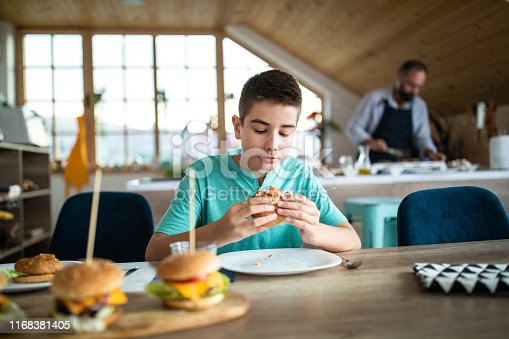 Teenage boy eating burgers for lunch, enjoying in food, while father baking burgers in the kitchen beside him