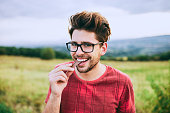 Teenage boy eating chocolate while standing in the meadow.