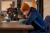 Teenage boy sitting at a kitchen table eating soup served by his father.